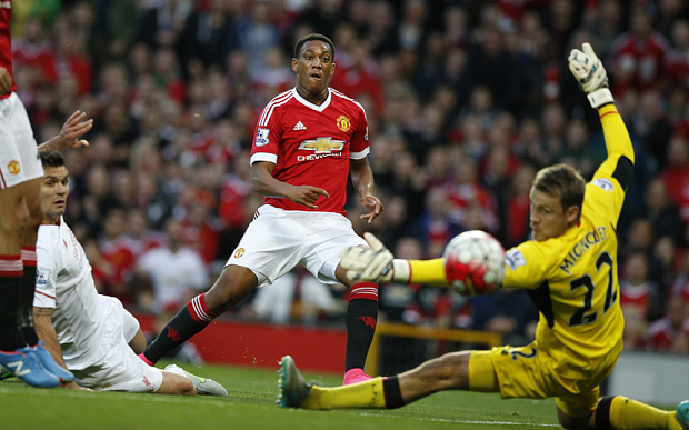 Manchester United's Anthony Martial scores past Liverpool's Simon Mignolet during the English Premier League soccer match between Manchester United and Liverpool at Old Trafford Stadium, Manchester, England, Saturday, Sept. 12, 2015. (AP Photo/Jon Super)